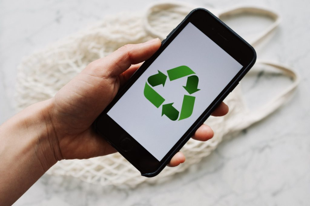 iPhone in einer Hand mit Recycling Icon